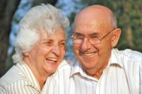 A husband and wife of 50 + years enjoy each other in the glow of a setting sun.